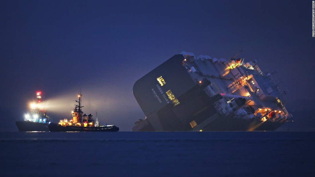 A tugboat lights the hull of the Hoegh Osaka cargo ship on Sunday, January 4. The cargo ship ran aground in the Solent, a strait near southern England. All 25 crew members were rescued overnight.