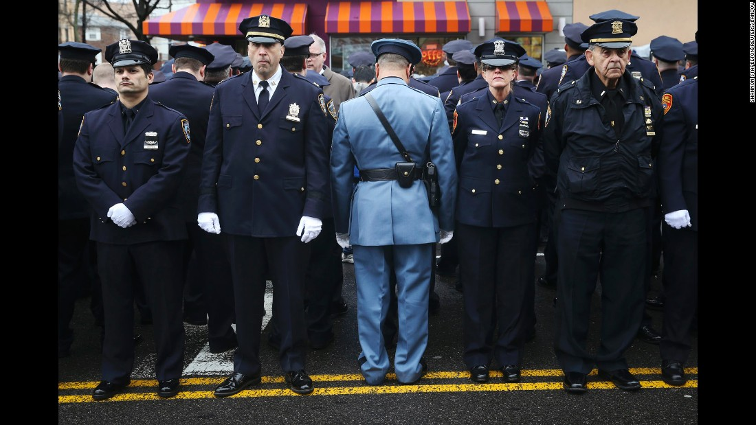 "Law enforcement officers stand outside <a href=""http://www.cnn.com/2015/01/04/us/gallery/liu-funeral/index.html"" target=""_blank"">the funeral of fallen New York police officer Wenjian Liu</a> on Sunday, January 4. Some officers turned their backs while New York Mayor Bill de Blasio spoke on a monitor. <a href=""http://www.cnn.com/2014/12/22/politics/de-blasio-police-shooting/index.html"" target=""_blank"">The mayor's critics</a> believe his comments after the death of Eric Garner contributed to an anti-police sentiment that led to the shootings of Liu and his partner, Rafael Ramos."