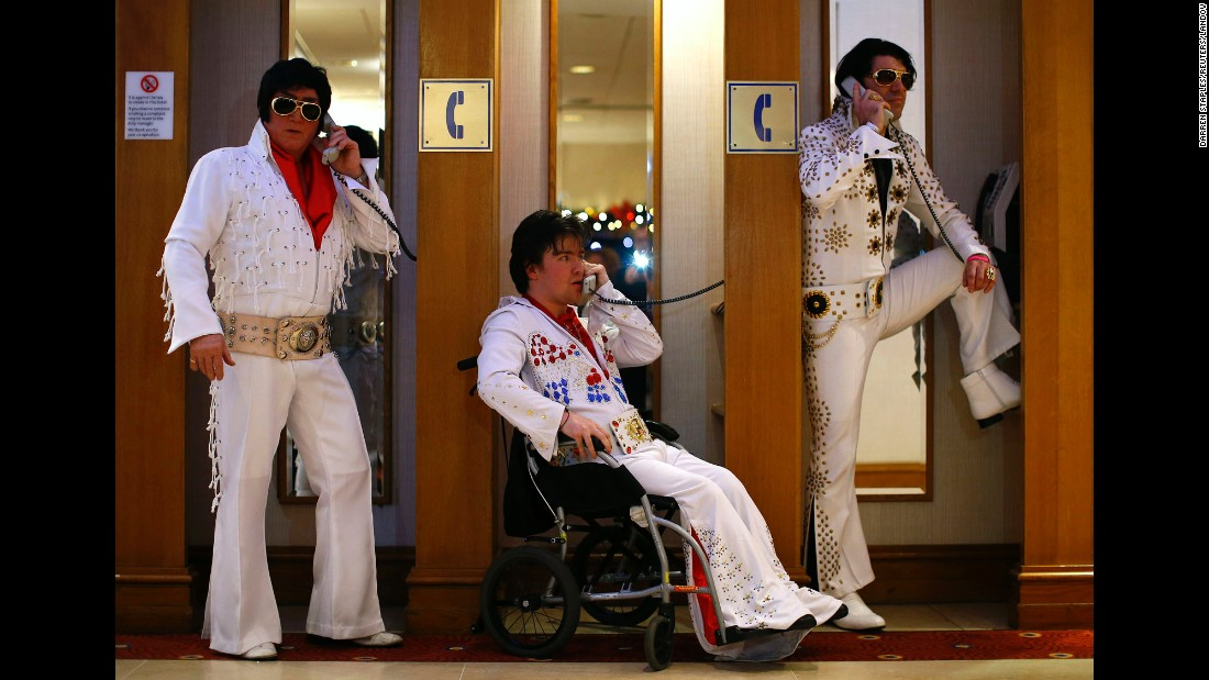 From left, Elvis Presley impersonators Phil Bailey, John Hindle and Eren Emir pose in telephone booths Friday, January 2, during an annual Elvis convention in Birmingham, England.