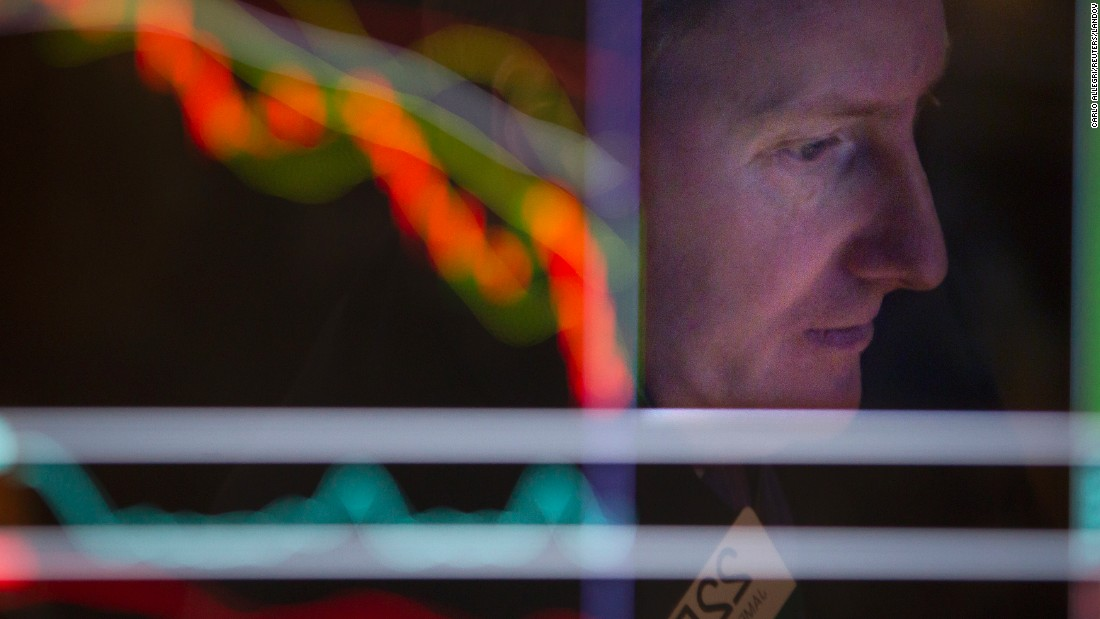 A trader is reflected on a screen as he works on the floor of the New York Stock Exchange on Friday, January 2.