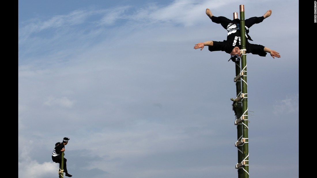 Members of a traditional firefighting preservation group perform ladder stunts Tuesday, January 6, during the annual New Year's Fire Brigade Review in Tokyo.