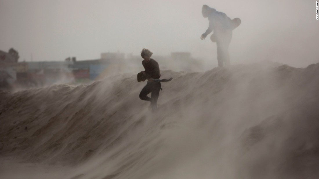 Kids play on a sand hill in Tel Aviv, Israel, that was made to block high waves ahead of a storm on Tuesday, January 6.