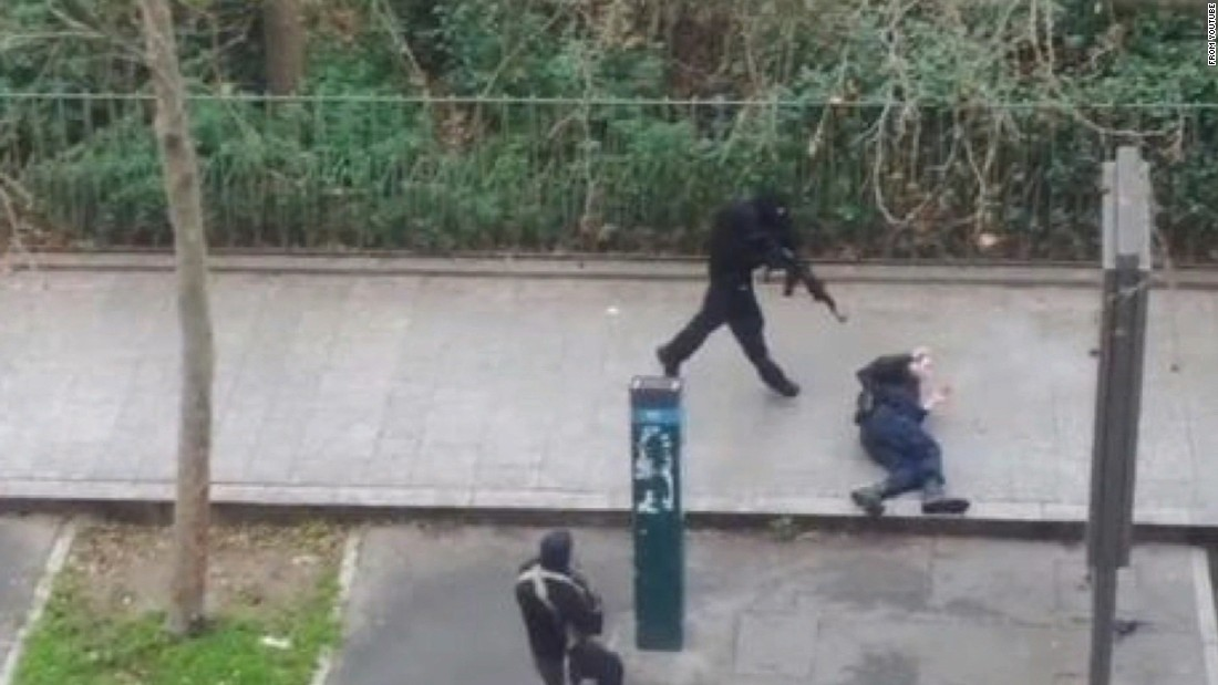 Masked gunmen run toward a victim in the Paris terror attack on Wednesday, January 7.