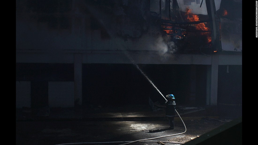 A firefighter sprays water at a shopping mall that was partially damaged Saturday, January 3, in Antiguo Cuscatlan, El Salvador.