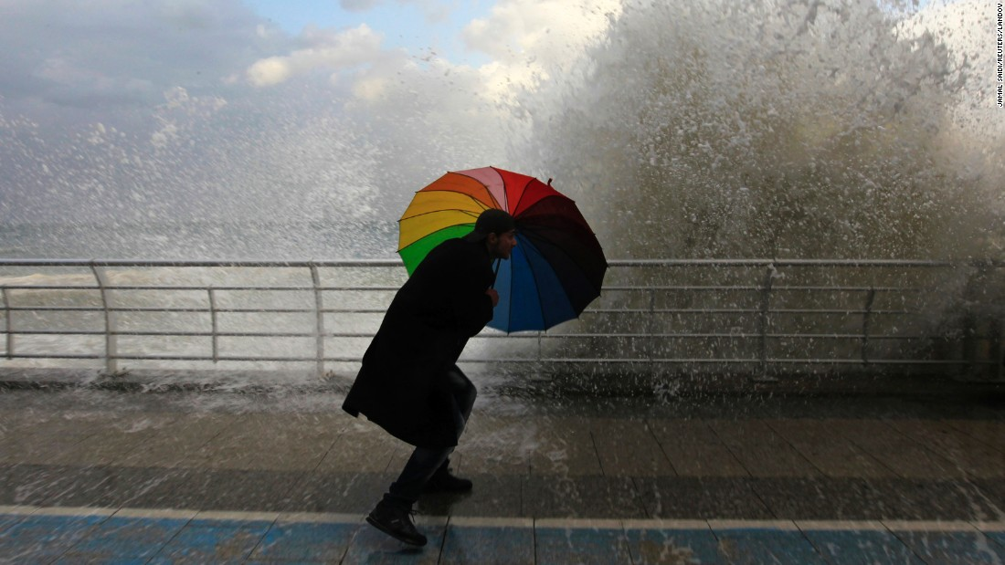 "A man in Beirut, Lebanon, plays in front of a wave crashing into the Corniche, a seaside promenade, on Tuesday, January 6. <a href=""http://www.cnn.com/2015/01/02/world/gallery/week-in-photos-0101/index.html"" target=""_blank"">See last week in 30 photos</a>"
