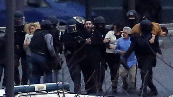 French police escort hostages away from the grocery store. At least 10 hostages managed to escape, according to a Paris police union spokesman.