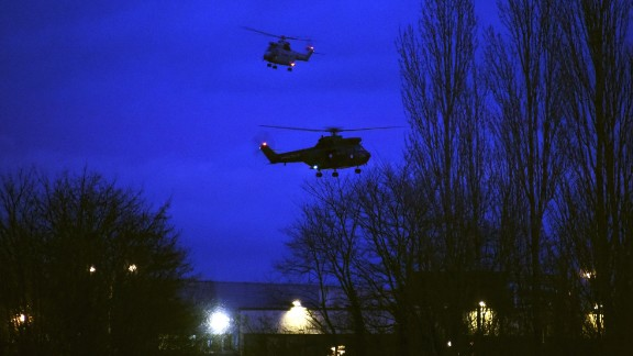 Helicopters fly over a printing shop in Dammartin-en-Goele, France, where there was a standoff Friday, January 9, between police and two men suspected in the Charlie Hebdo shootings earlier this week. Cherif and Said Kouachi, the two brothers wanted in the case, were killed by security forces, authorities said.