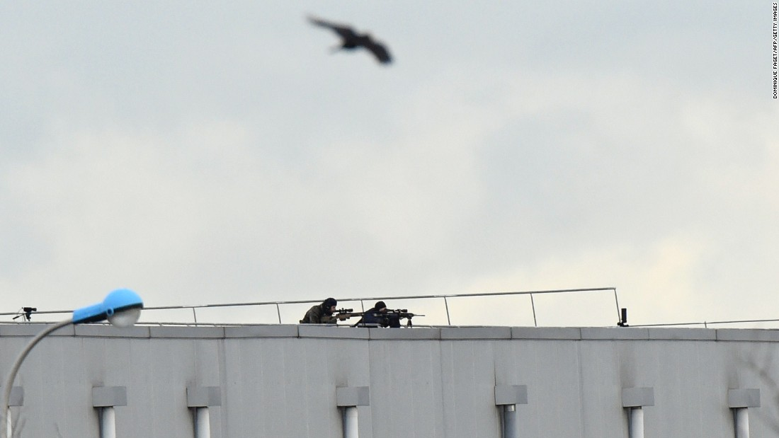 A bird flies overhead as police snipers take aim from a roof.