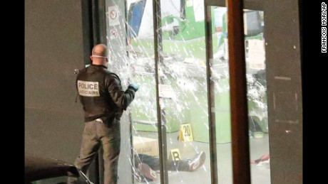 A police officer closes the bullet ridden door next to a body lying in a kosher market in Paris on Friday, January 9.