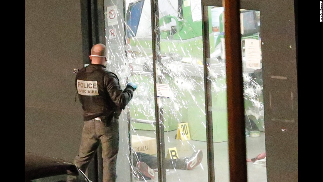A police officer closes the bullet ridden door next to a body lying in a kosher grocery store in the Paris neighborhood of Porte de Vincennes on Friday, January 9. Amedy Coulibaly -- the man who authorities believe killed a policewoman Thursday south of Paris -- was killed when police stormed the store. A search is underway for suspected accomplice, a woman identified as Hayat Boumeddiene. <br />