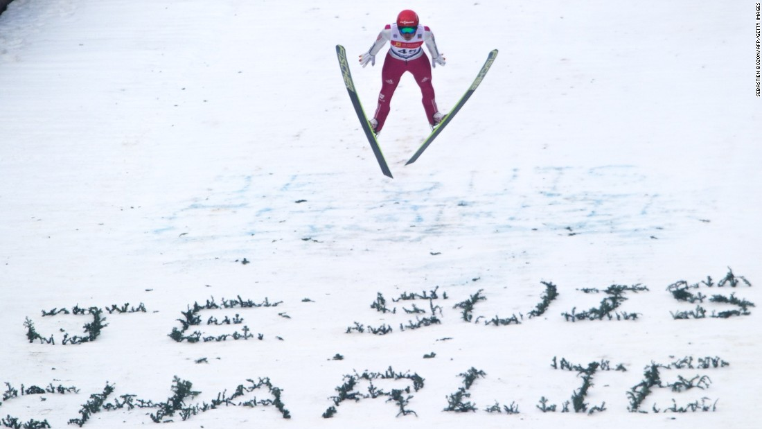 Norway's Jan Schmid soars through the air over a 'Je suis Charlie' message created in the snow at a World Cup Nordic Combined skiing event in eastern France.