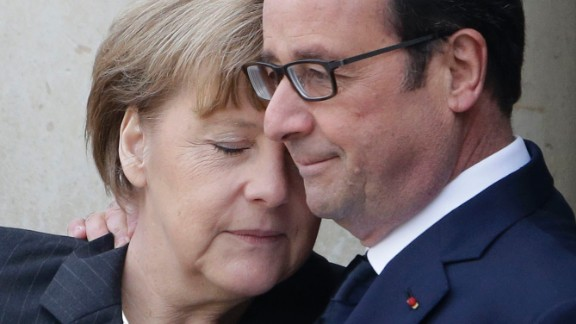 French President Francois Hollande hugs German Chancellor Angela Merkel as she arrives at the Elysee Palace before the rally.
