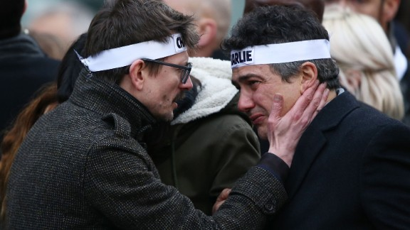 """Charlie Hebdo cartoonist Renald """"Luz"""" Luzier, left, speaks to Charlie Hebdo journalist Patrick Pelloux during the rally. Luzier is the only surviving cartoonist left at the magazine."""