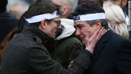 "Patrick Pelloux (right), a journalist at Charlie Hebdo, is embraced by Renald ""Luz"" Lucier (left), a cartoonist at the magazine."
