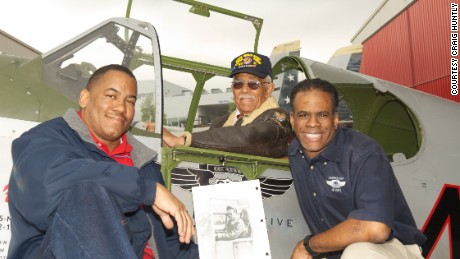 Clarence Huntley Jr., center, poses in the cockpit of a P-51 Mustang with his nephew, Craig Huntly, left, and Brad Lang. Craig Huntly holds a photo of his uncle in 1944.