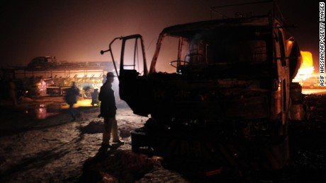A Pakistani policeman stands beside wreckage of a burnt out oil tanker and passenger bus on the Super Highway near Karachi early on January 11, 2015.