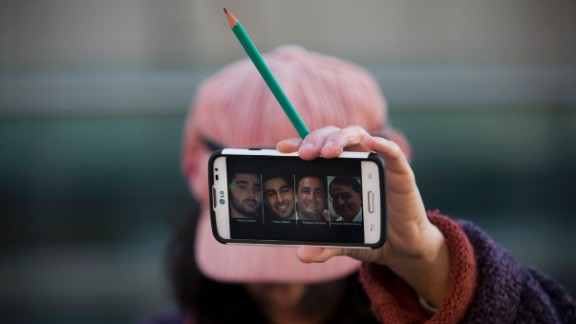A woman in Tel Aviv, Israel, holds a pencil Sunday, January 11, showing solidarity for the 12 people who were killed in a shooting last week at the Paris office of French satirical magazine Charlie Hebdo. Her cell phone shows four people who were killed in a Paris standoff several days after the Charlie Hebdo attack.