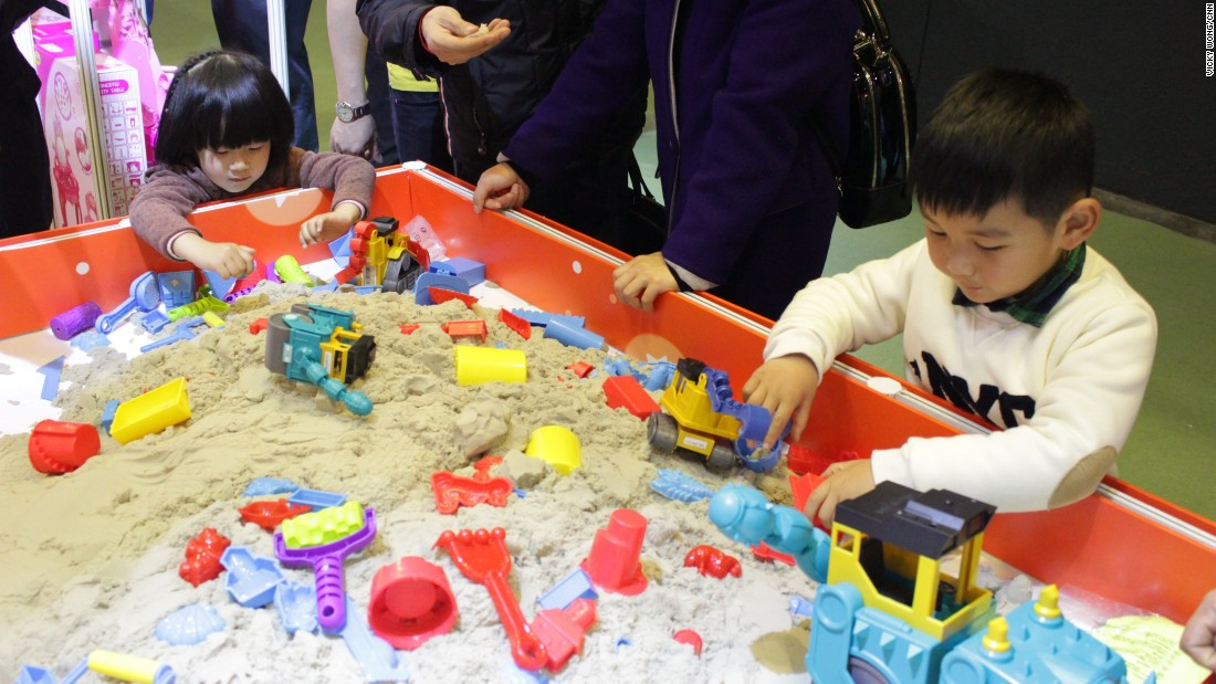 Two children play with kinetic sand, a mess-free and easy to shape alternative to a traditional sandbox. The fair organizers said more than 2,700 exhibitors and 8,700 buyers from around the world attended the three-day fair.