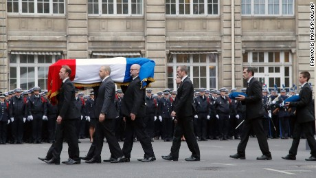 French police officers carry the coffin of Police officer Franck Brinsolaro, killed at Charlie Hebdo during a ceremony to pay tribute to the three police officers killed in the attacks, in Paris, France, Tuesday, Jan. 13, 2015.  Police officers Ahmed Merabet, 40, Franck Brinsolaro, 49, were killed during the attacks at Charlie Hebdo, and Clarissa Jean-Philippe killed in Montrouge last week. (AP Photo/Francois Mori, pool)