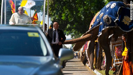 Pope Francis waves to people waiting on the road after crossing a row of decorated elephants standing to welcome him in Colombo, Sri Lanka, Tuesday, January 13, 2015.