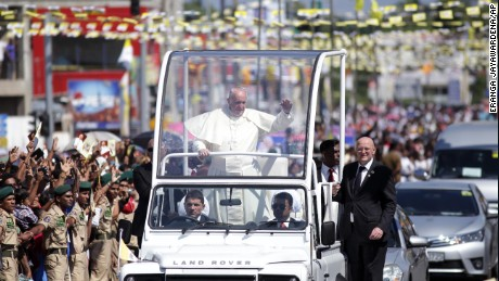 Pope Francis waves to people waiting on the road standing to welcome him on the outskirts of Colombo, Sri Lanka, Tuesday, January 13, 2015.
