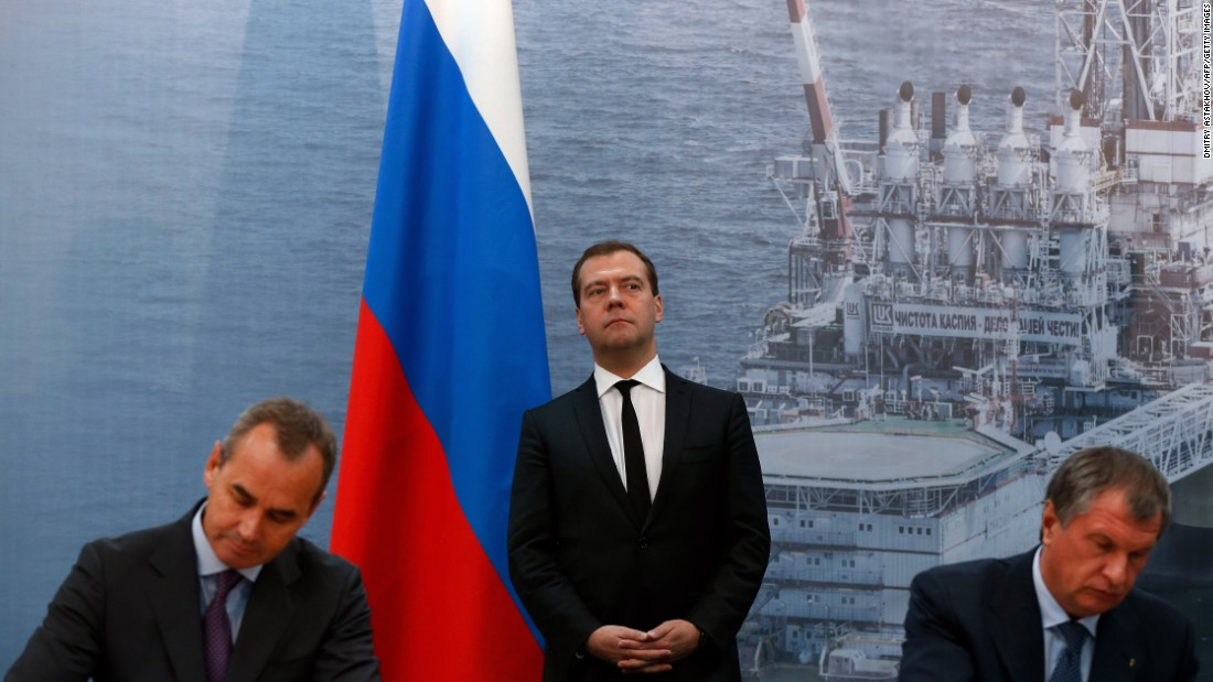 Russia's Prime Minister Dmitry Medvedev (C) stands in front of the huge photo of a fixed offshore ice-resistant platform of the oil giant Lukoil during a signing ceremony between Russia's Rosneft oil company and Sweden's Lundin Petroleum in the Russian Caspian Sea port of Astrakhan, on October 2, 2013