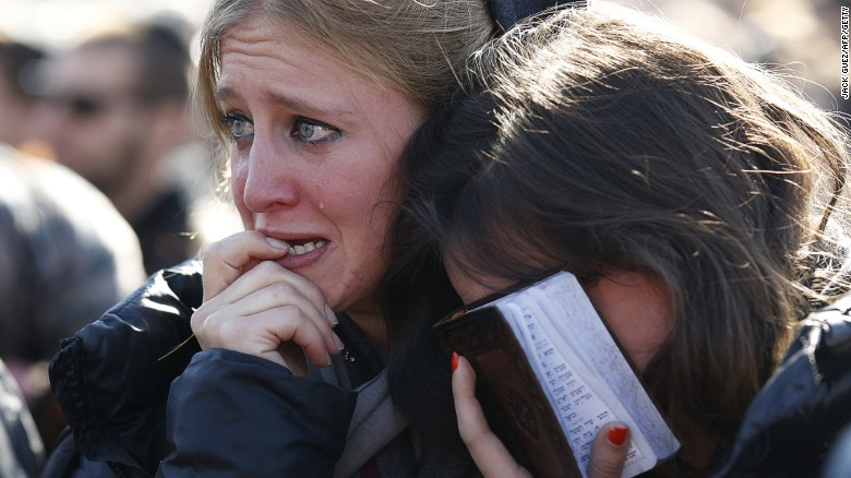 Mourners grieve and a Jewish woman clings to a prayer book during the Tuesday funeral in Jerusalem for the four French Jews killed in an Islamist attack on a kosher supermarket in Paris last week.