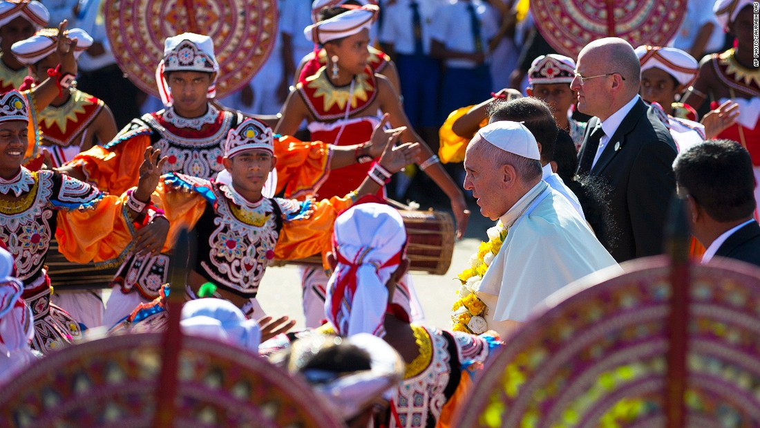 "JANUARY 13 - COLOMBO, SRI LANKA: Pope Francis walks past colorful dancers upon his arrival in Colombo. This is the first leg of the pontiff's week-long trip to Asia, where he was received at the airport by <a href=""http://cnn.com/2015/01/08/asia/sri-lanka-elections-walkup/"">newly-elected President Maithripala Sirisena</a> and Cardinal Malcolm Ranjith."