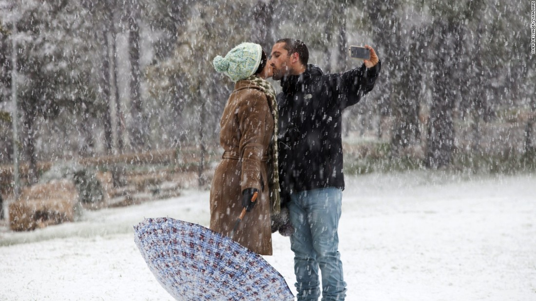 A couple shares a kiss Friday, January 9, in a snow-covered park in Jerusalem.