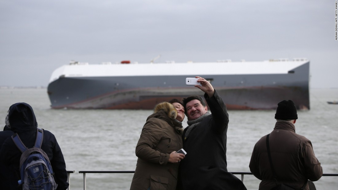 Ferry passengers take a photo together as they pass the grounded Hoegh Osaka cargo ship on Wednesday, January 7. The cargo ship ran aground in the Solent, a strait near southern England, several days earlier.