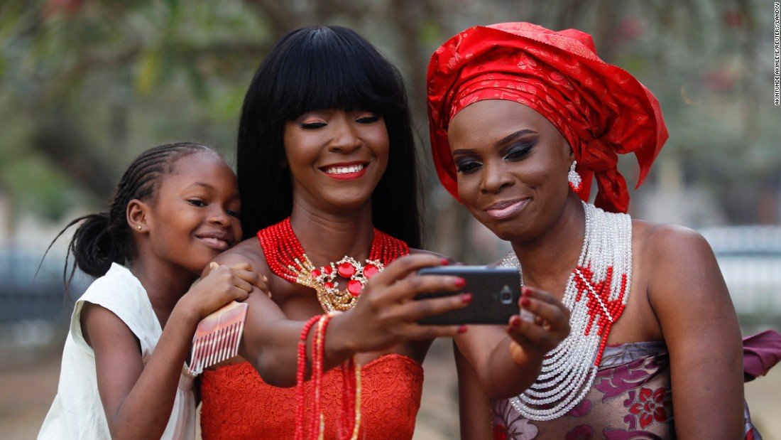 Models in Lagos, Nigeria, take selfies as they display neck beads at a park on Sunday, January 11.