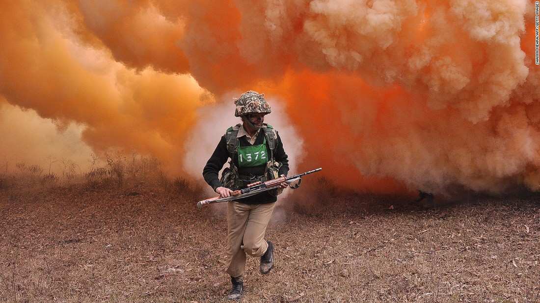 JANUARY 14 - HOSHIARPUR, INDIA: An Indian Border Security Force (BSF) female commando runs from thick smoke during an exercise at the Kharkan Training Camp, around 60 kms from Jalandhar. The BSF is a paramilitary force charged with guarding India's land border in peacetime and preventing transnational crime.