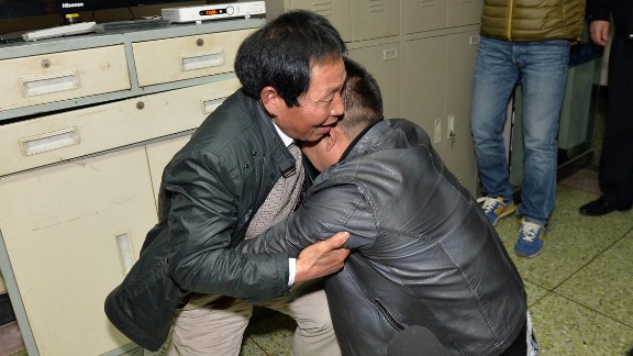 Sun Bin, right, who was abuducted in 1991 at the age of 4, kneels down and hugs his father Sun Youhong after they reunited in an office at the Chengdu Public Security Bureau in Chengdu city, southwest China