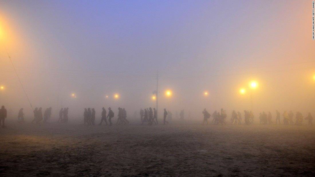 JANUARY 15 - ALLAHABAD, INDIA: Indian Hindu devotees arrive during a cold and foggy morning to take a holy dip for the Makar Sankranti festival. The annual Magh Mela gathering takes place at Sangam, the confluence of the rivers Ganges, Yamuna and the legendary Saraswati.