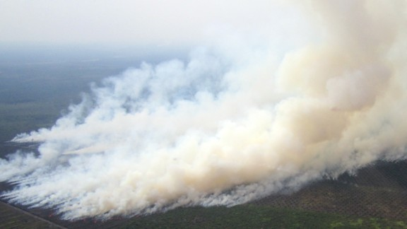 """Smoke billowing from fires in areas surrounded by plantations in Riau province, on Indonesia's Sumatra island, about 173 miles west of Singapore on June 17 2013. On June 20, Singapore demanded """"definitive"""" action by Indonesia on forest fires raging in Sumatra as the nations prepared for emergency talks to ease the severe smog enveloping Singapore."""