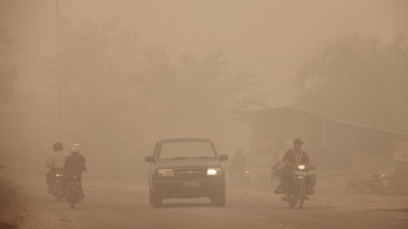 Indonesian motorists travel under a blanket of haze in Dumai town, Riau province, March 3, 2014.