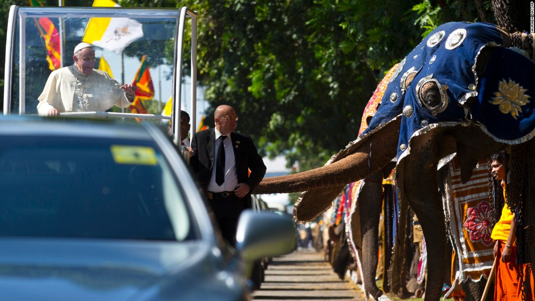 "Pope Francis waves as he passes a row of decorated elephants in Colombo, Sri Lanka, on Tuesday, January 13. It was the first stop on <a href=""http://www.cnn.com/2015/01/13/world/gallery/pope-in-asia/index.html"" target=""_blank"">his weeklong trip to Asia.</a>"