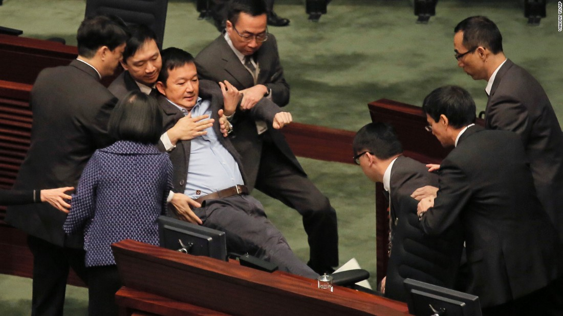 Pro-democracy legislator Raymond Chan is taken away by security guards after he protested against Hong Kong Chief Executive Leung Chun-ying during Leung's annual policy address on Wednesday, January 14.