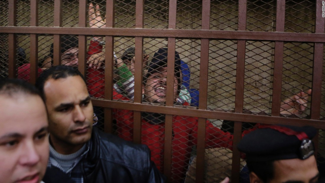 "Police surround a courtroom cell in Cairo as men celebrate being acquitted of ""debauchery"" on Monday, January 12. The 26 men were arrested last month by police looking for gay people at a public bathhouse. The arrests caused an uproar among activists and rights groups."