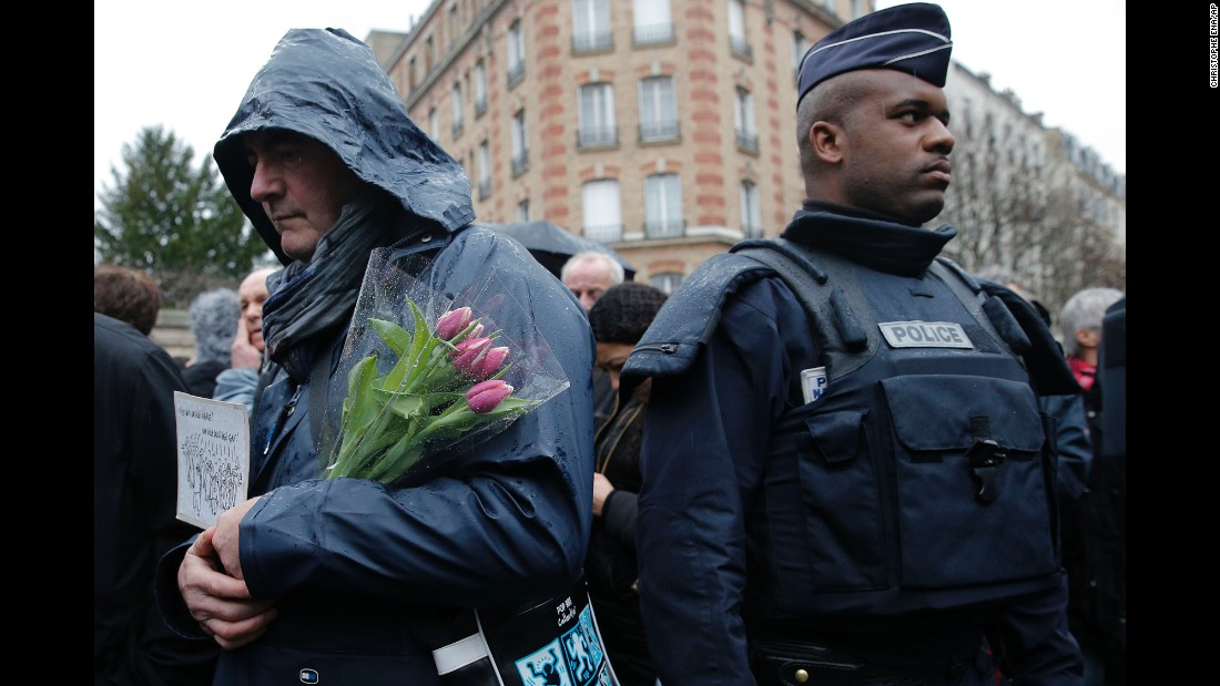 A man waits to enter the Pere Lachaise cemetery in Paris during Verlhac's funeral on January 15.