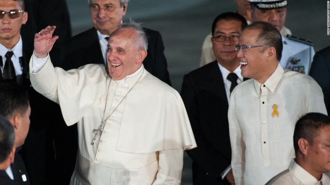 Pope Francis waves to the crowd with Philippine President Benigno Aquino upon his arrival in the Philippines on January 15 in Manila, Philippines.