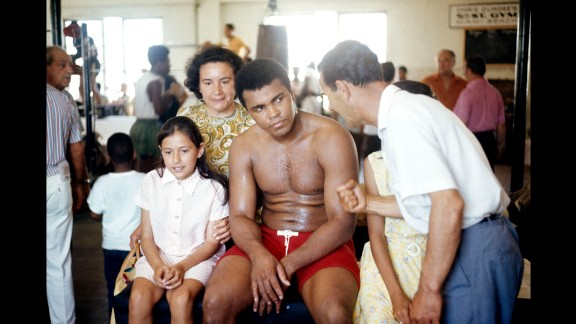 Ali sits with young fans in the gym while listening to his trainer, Angelo Dundee.