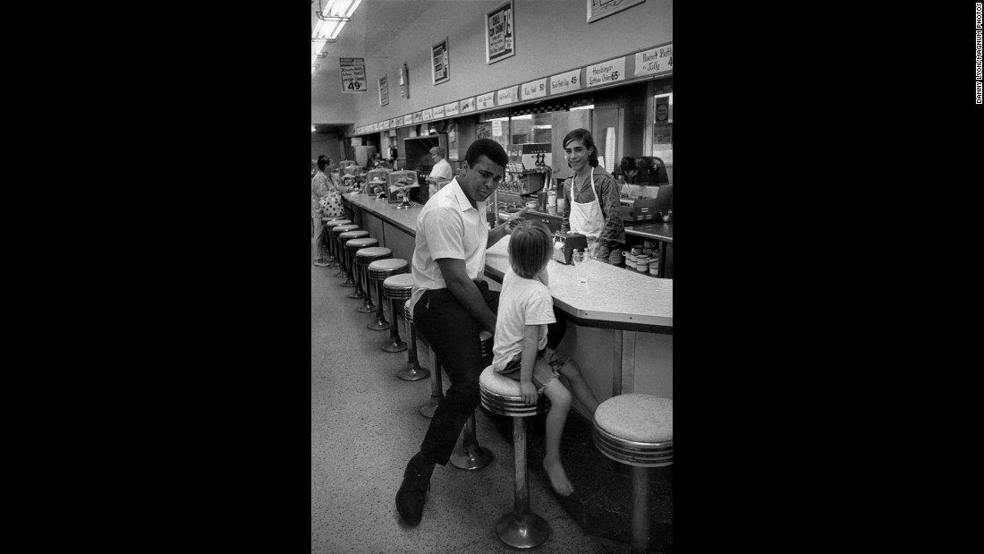 Ali sits with a child at a restaurant counter.