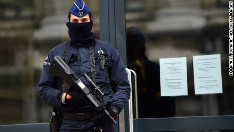 An armed policeman stands guard at the entrance of Belgium's federal prosecutor office in Brussels, January 16, 2015. Belgian police arrested 13 people during a dozen raids overnight, smashing plot to kill police officers 'in public roads and in police stations', prosecutors said.