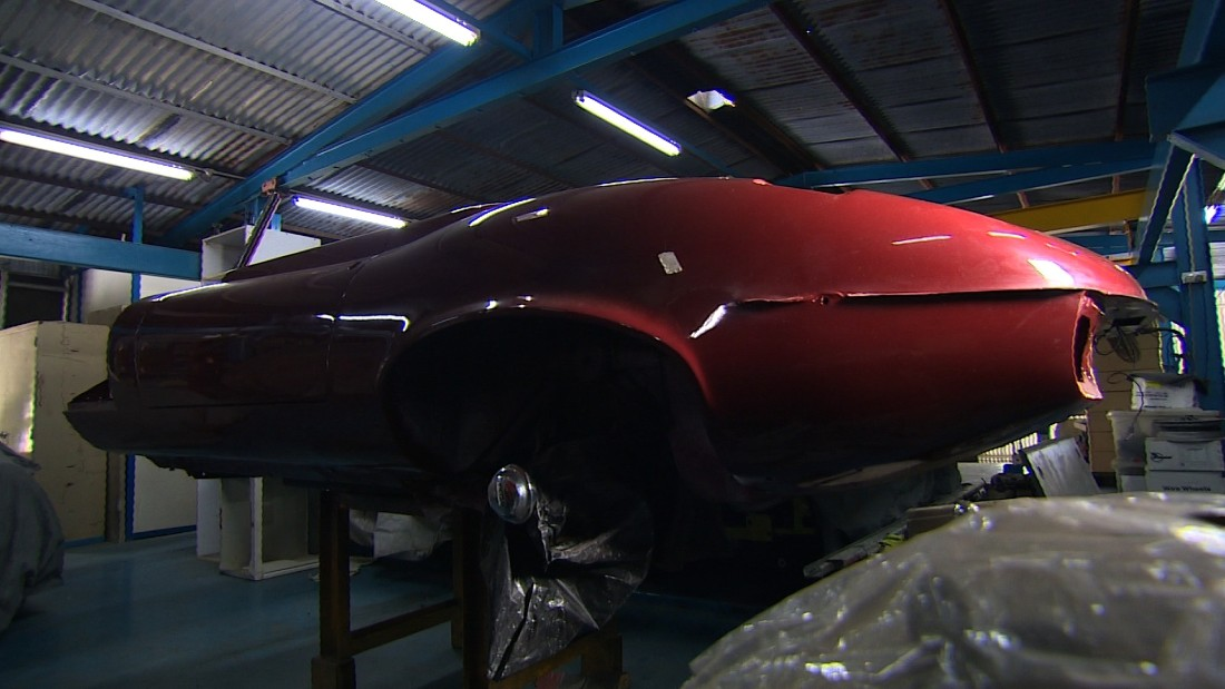 He heavily invests in the maintenance of his cars, such as this deep red Jaguar from the 1970s which is currently being repaired.