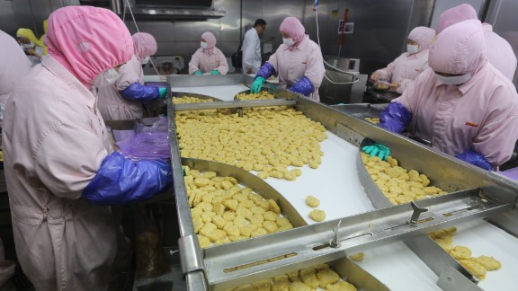 Workers producing food at a factory in Shanghai.