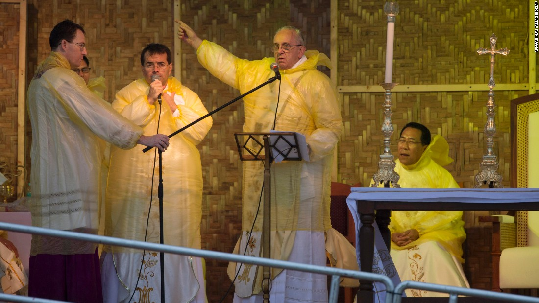 "Pope Francis points at the statue of Jesus during his speech as he celebrates a mass in Tacloban, on Saturday, January 17.  A rain-drenched but lively crowd wearing yellow and white raincoats welcomed Pope Francis to the typhoon-ravaged central city of Tacloban, chanting ""Papa Francesco, Viva il Papa!"""