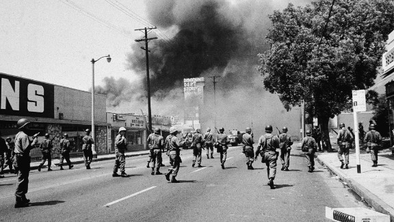 Armed National Guardsmen march toward smoke on the horizon during the street fires of the Watts riots, Los Angeles, August 1965.