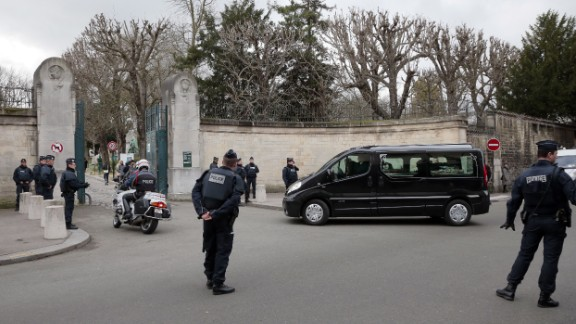 """Police stand by as a hearse carrying Mustapha Ourrad's coffin arrives at the Pere Lachaise cemetery in Paris on Friday, January 16. Ourrad, a copy editor for the satirical magazine Charlie Hebdo, was one of 12 people killed in a <a href=""""http://www.cnn.com/2015/01/07/world/gallery/paris-charlie-hebdo-shooting/index.html"""" target=""""_blank"""">terror attack</a> on the magazine's office."""