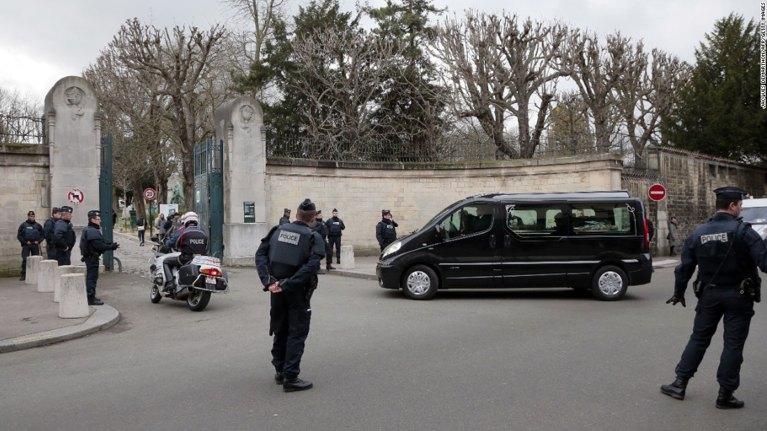 "Police stand by as a hearse carrying Mustapha Ourrad's coffin arrives at the Pere Lachaise cemetery in Paris on Friday, January 16. Ourrad, a copy editor for the satirical magazine Charlie Hebdo, was one of 12 people killed in a <a href=""http://www.cnn.com/2015/01/07/world/gallery/paris-charlie-hebdo-shooting/index.html"" target=""_blank"">terror attack</a> on the magazine's office."